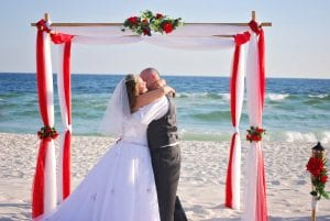 Destin Florida beach wedding ceremony with red and white bamboo canopy.