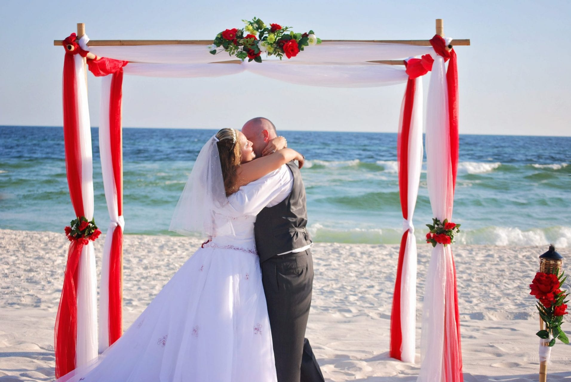 Just married couple kisses under wedding arch on Destin Gulf beach, FL