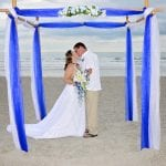 A romantic kiss under a blue and white canopy in this all inclusive package at our Destination Weddings in Florida package.
