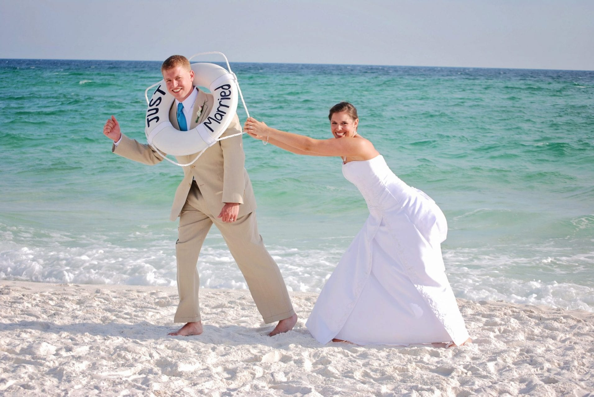 Couple plays with life preserver on Destin beach after wedding