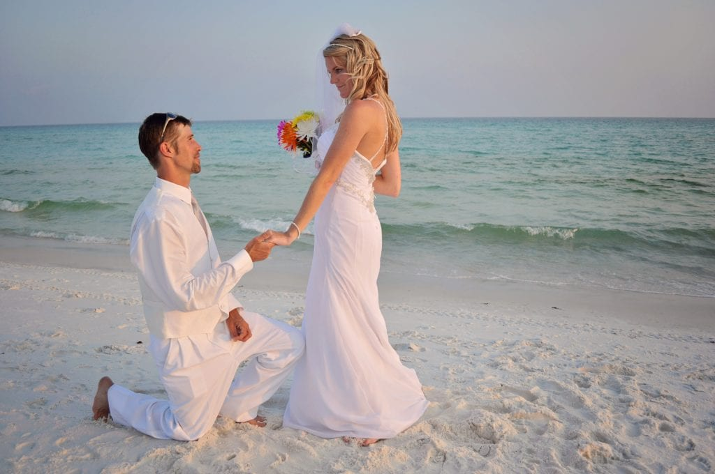 Groom kneels before bride at Destin beach barefoot wedding in Florida