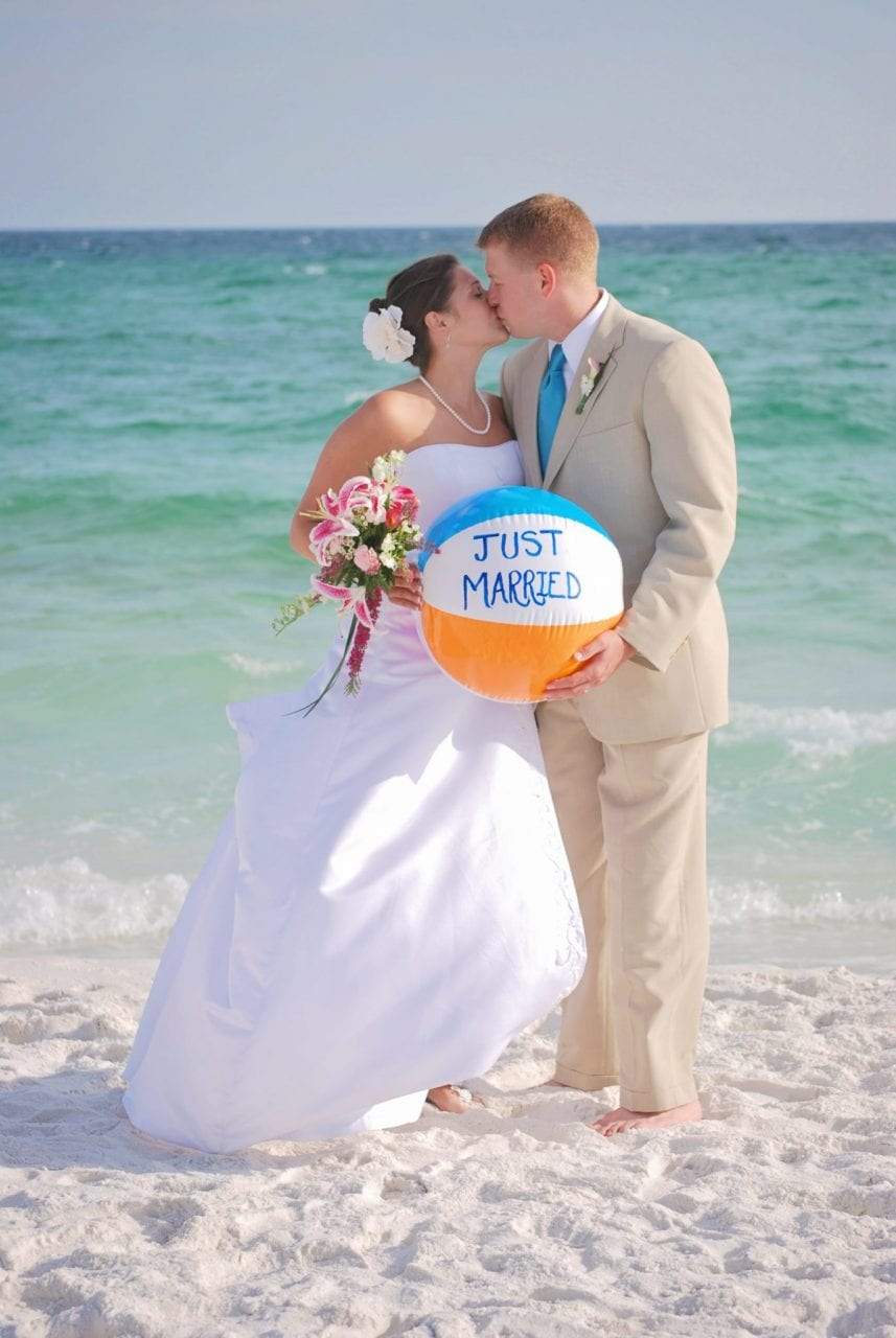 Wedding couple kissing with beach ball in Pensacola, FL