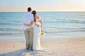 a bride and groom stare at the sunset of their Siesta Key Beach weddings.
