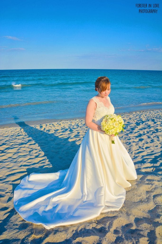 Bride holds yellow bouquet while posing on Cocoa Beach FL