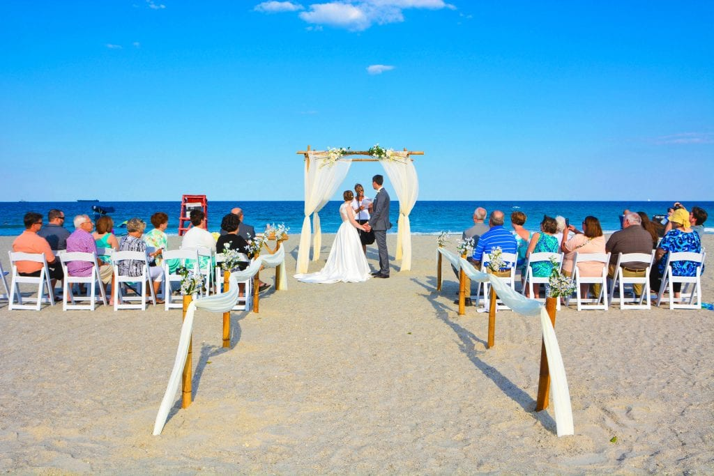 Couple on beach saying vows with wedding guests.