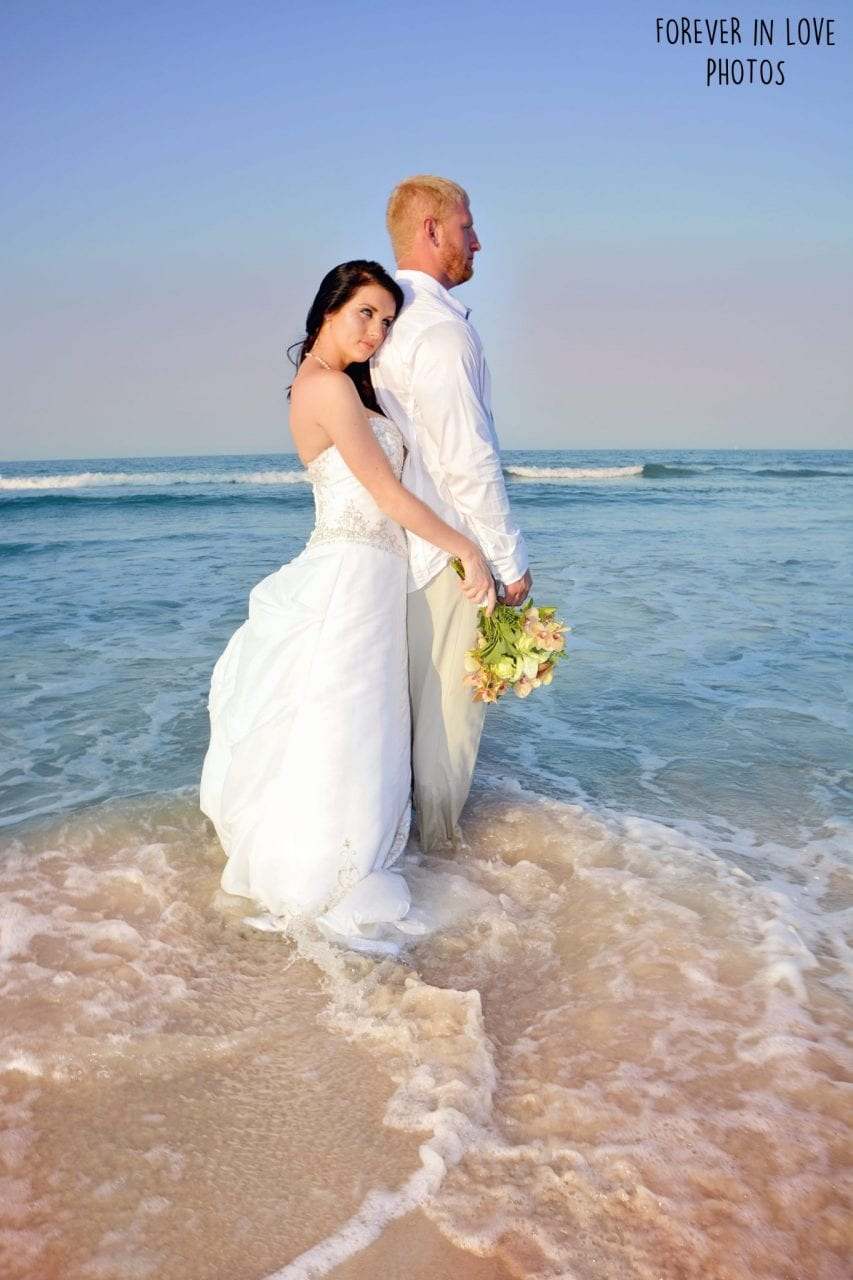 Couple standing in the ocean after beach wedding