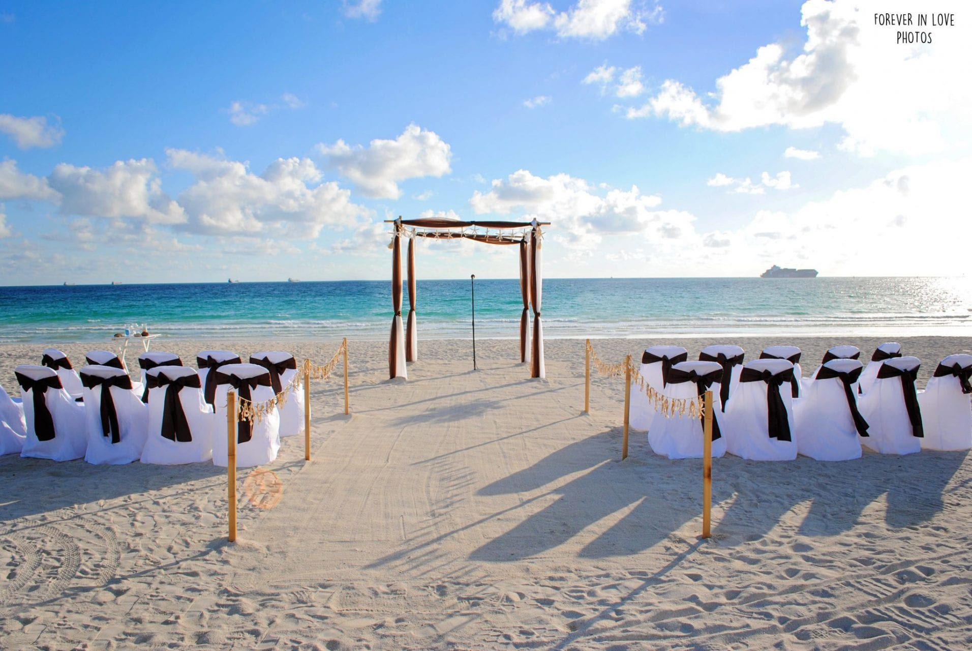 Beautiful beach wedding arch with white chairs on Miami Beach