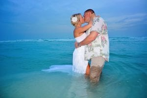 A bride and groom stand in the ocean during one of our Siesta Key Beach Weddings.