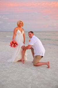 A groom takes off the brides garter during Siesta Key Beach Weddings