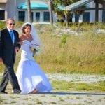 Siesta Key Beach Weddings include traditions such as this bride being walked down the aisle by her father.