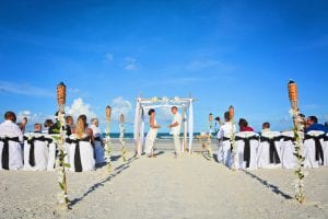 Lily draped tiki torches line the isle way as they say their vows at one of the Destination Weddings in Florida.