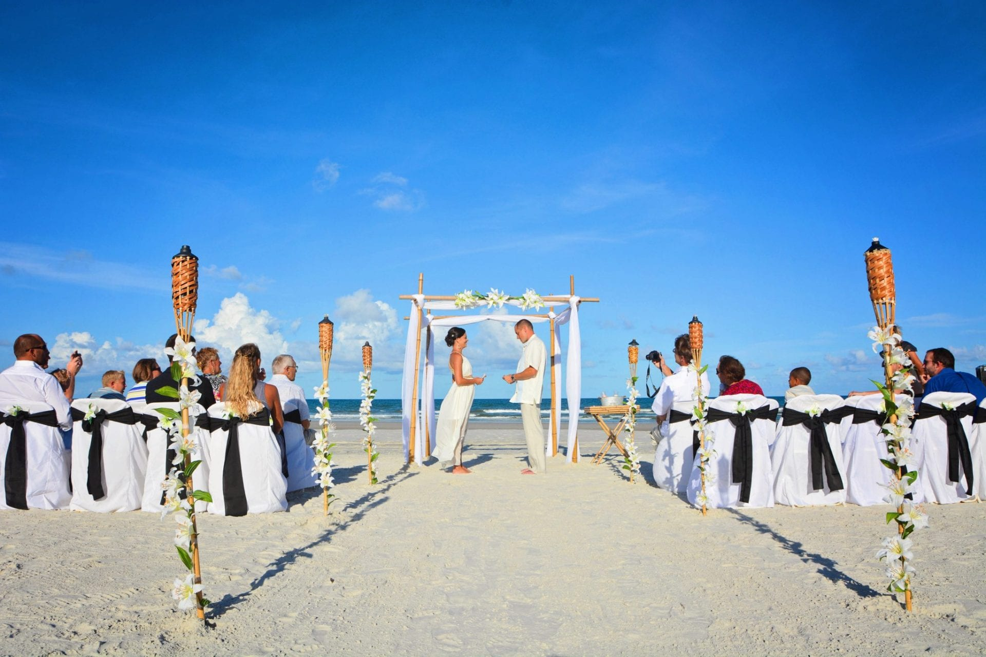 Couple says vows on Jacksonville Beach under bamboo wedding canopy