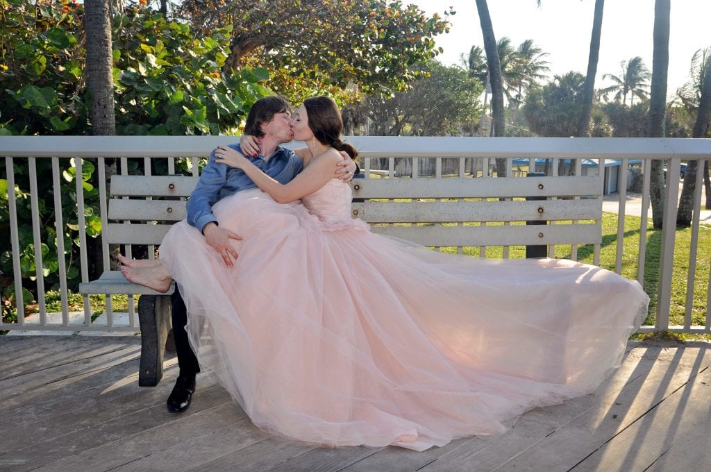 Miami Beach bride and groom kissing after wedding on park bench