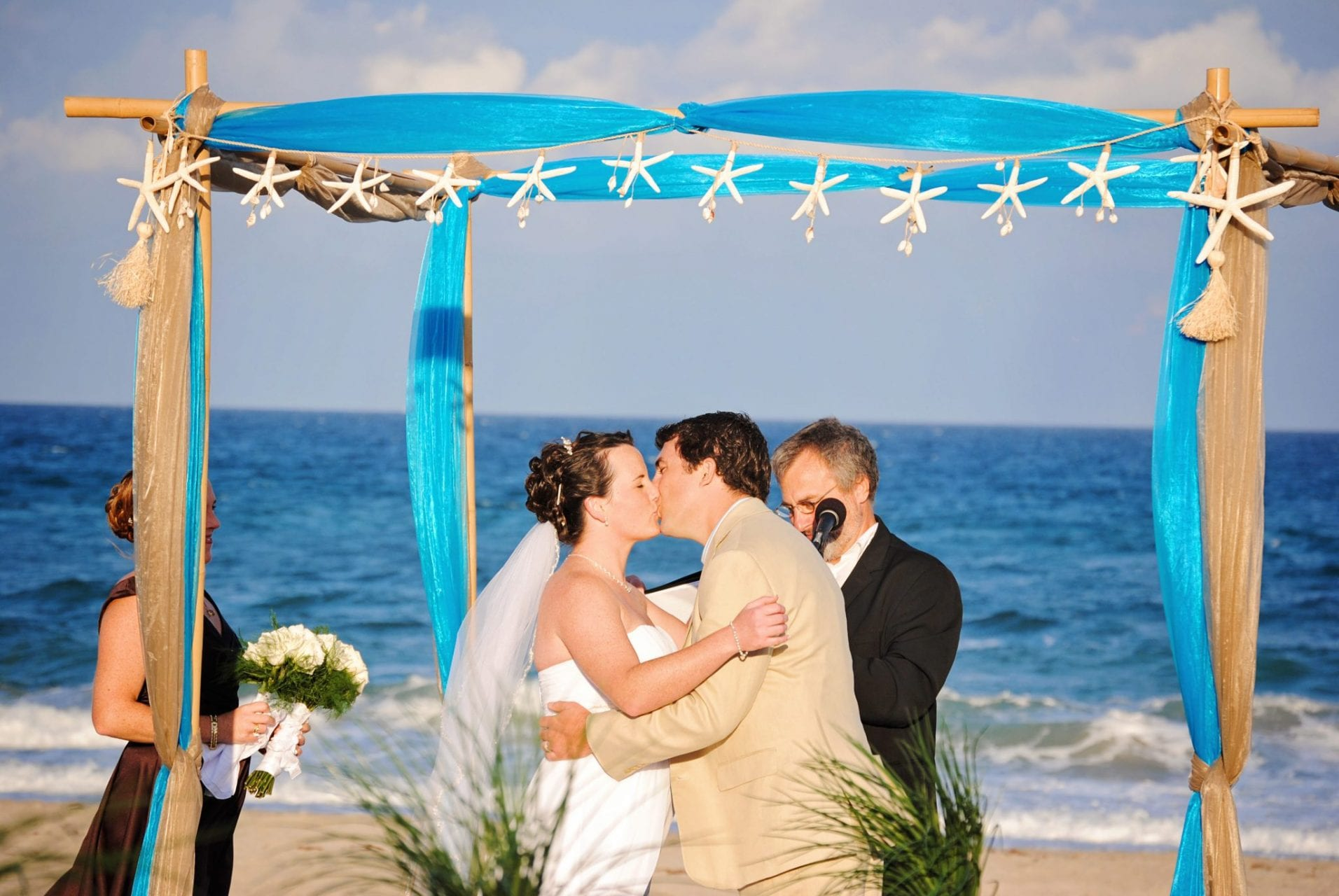Couples kisses under wedding arch in Boynton Beach, FL, Palm Beach
