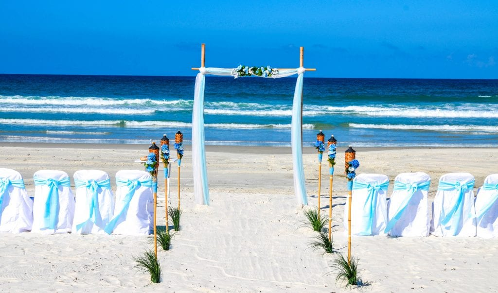 Blue wedding arch with chairs set up by ocean on Daytona Beach