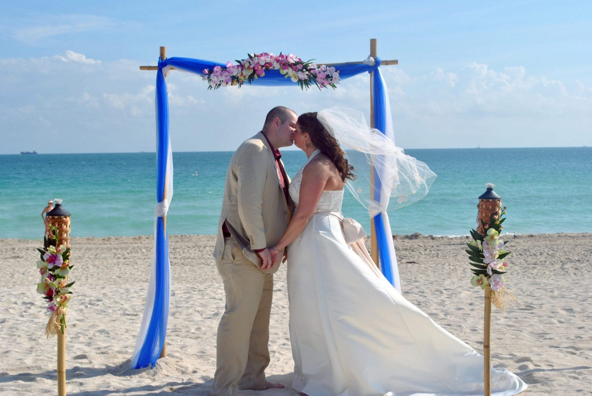 Couple kissing after Miami Beach wedding under arch on beach