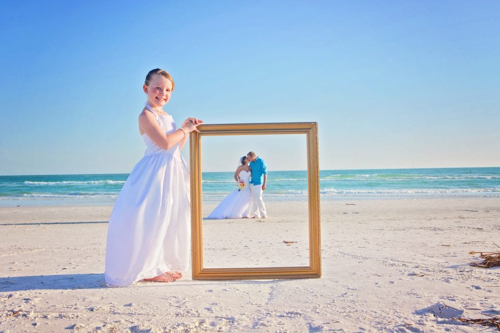 A bride and groom pose behind a frame of their child during our Siesta Key Beach Weddings.