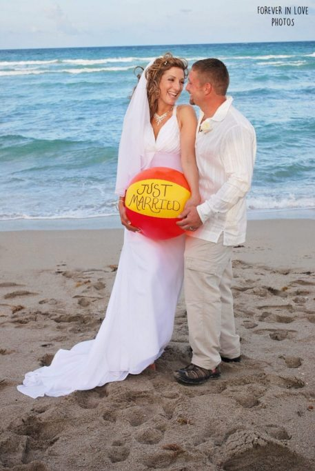 Couple after Miami beach wedding holds beach ball