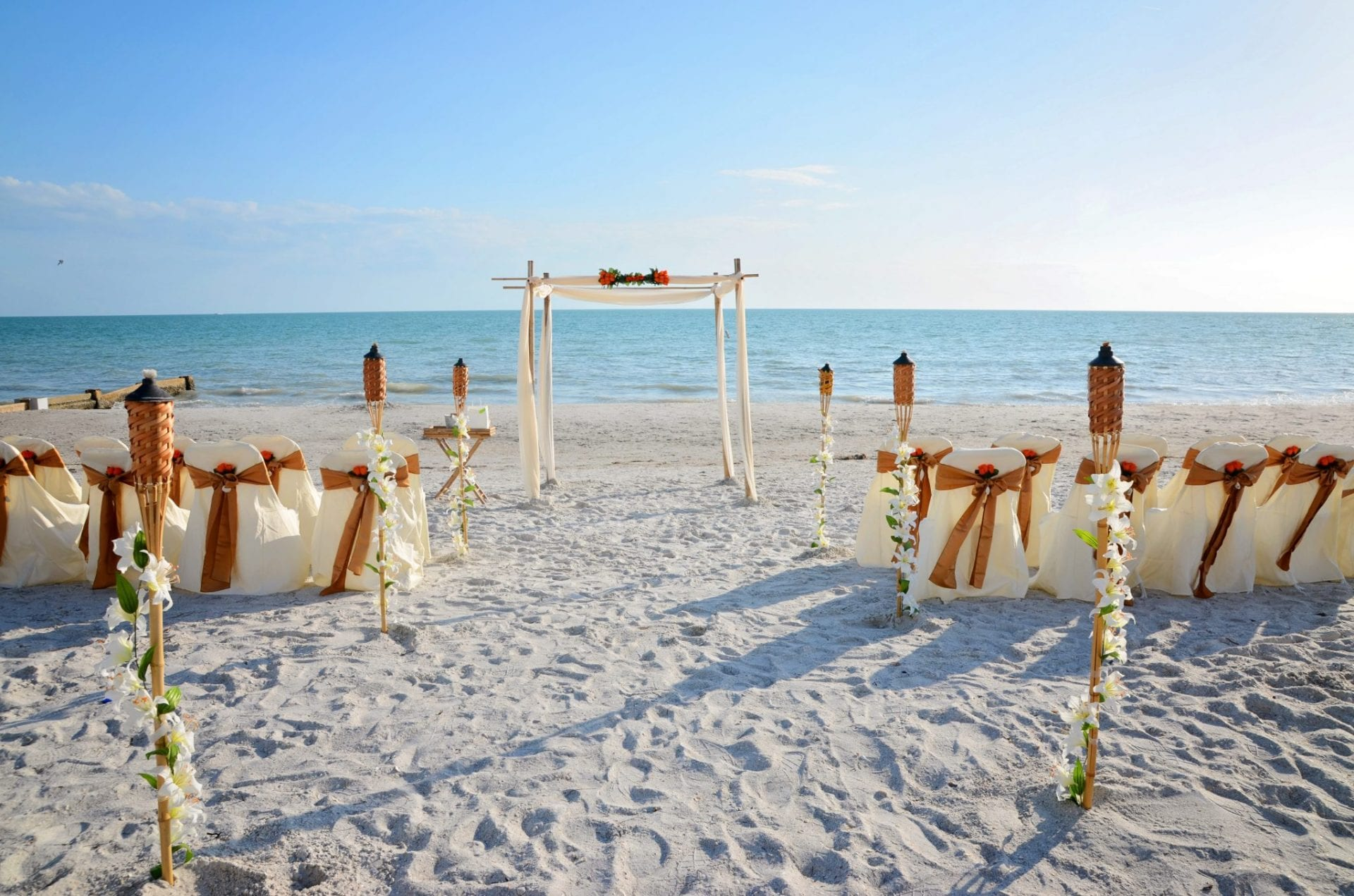 Wedding arch with chairs and tiki torches on Miami Beach