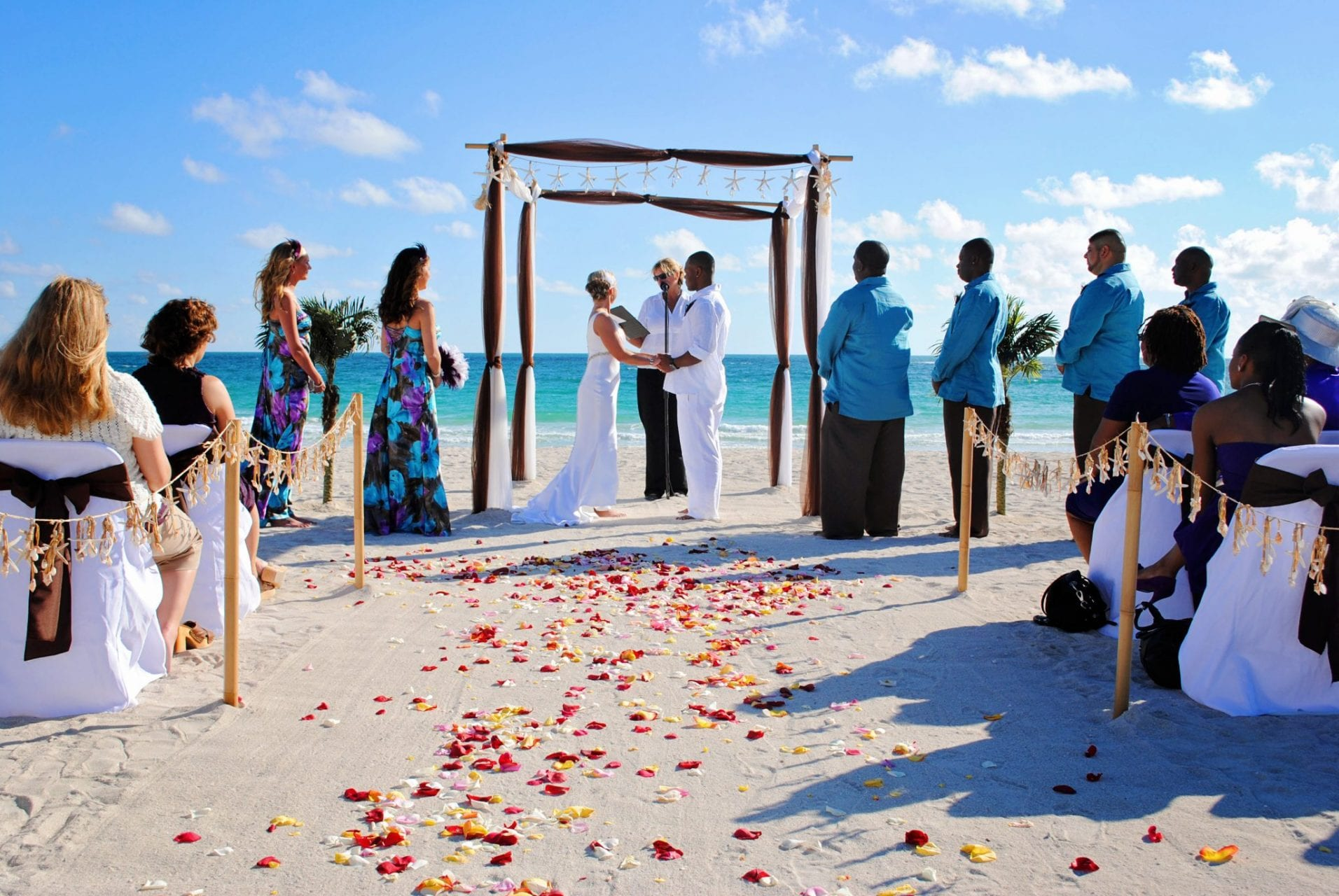 Couple saying vows with rose petals by the ocean in Miami