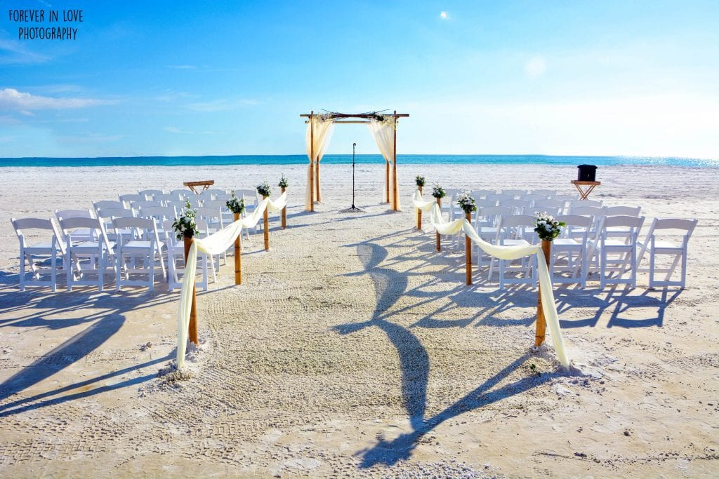 Wedding in Florida with white chairs and natural beach wedding canopy.