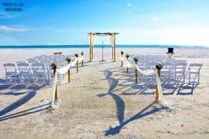 Weddings in Florida with white chairs and natural beach wedding canopy.