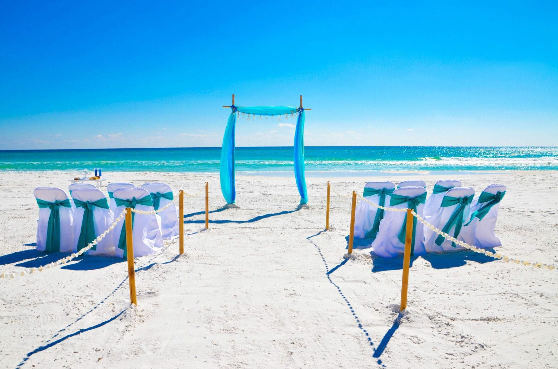 Teal blue beach wedding arch and chairs
