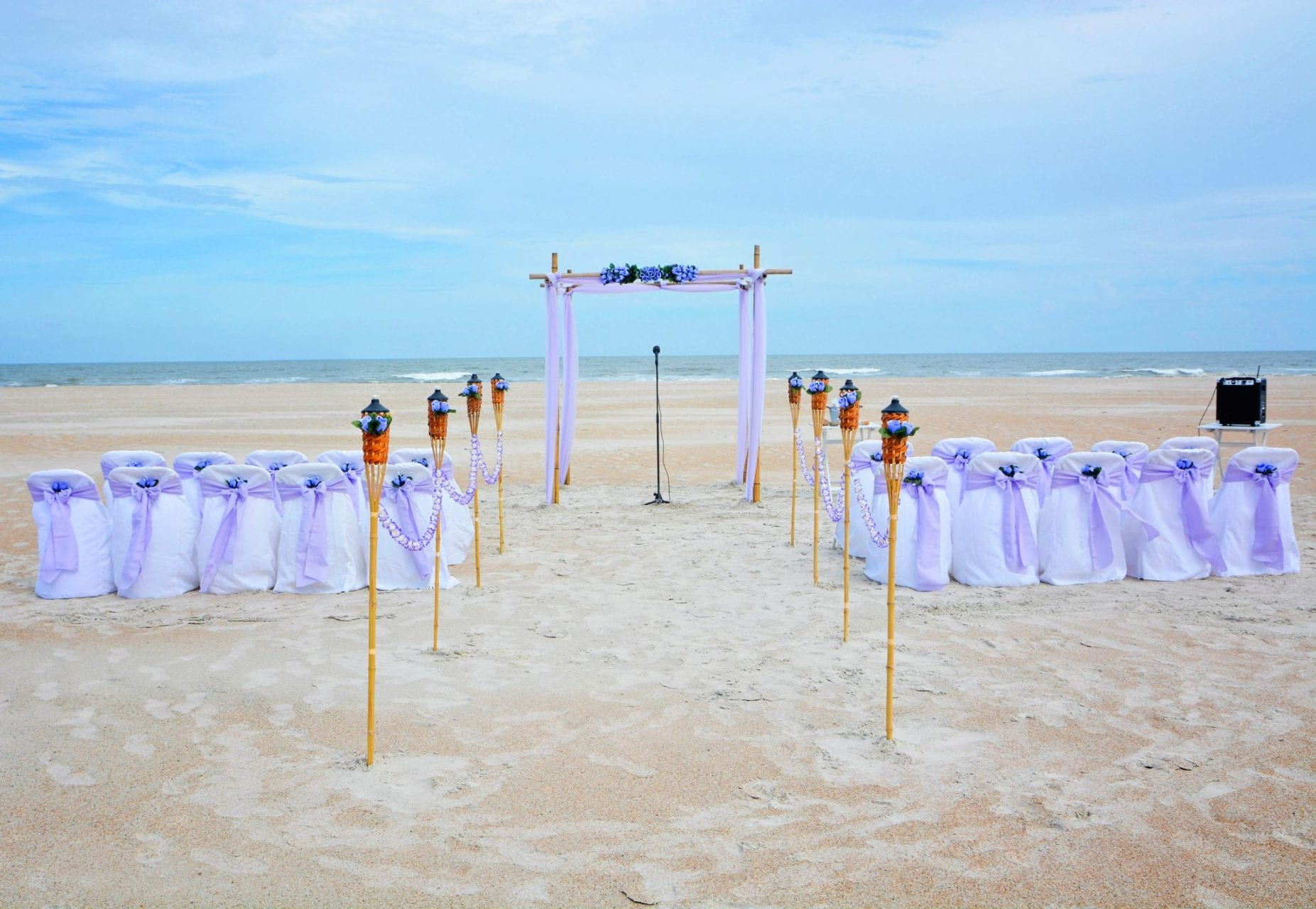 Wedding alter on the beach with tiki torch