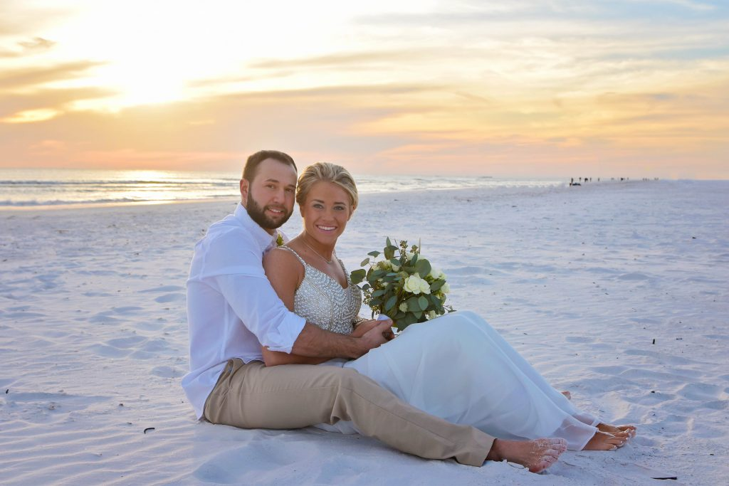 Couple sitting on sand after beach wedding Siesta Key with sunset