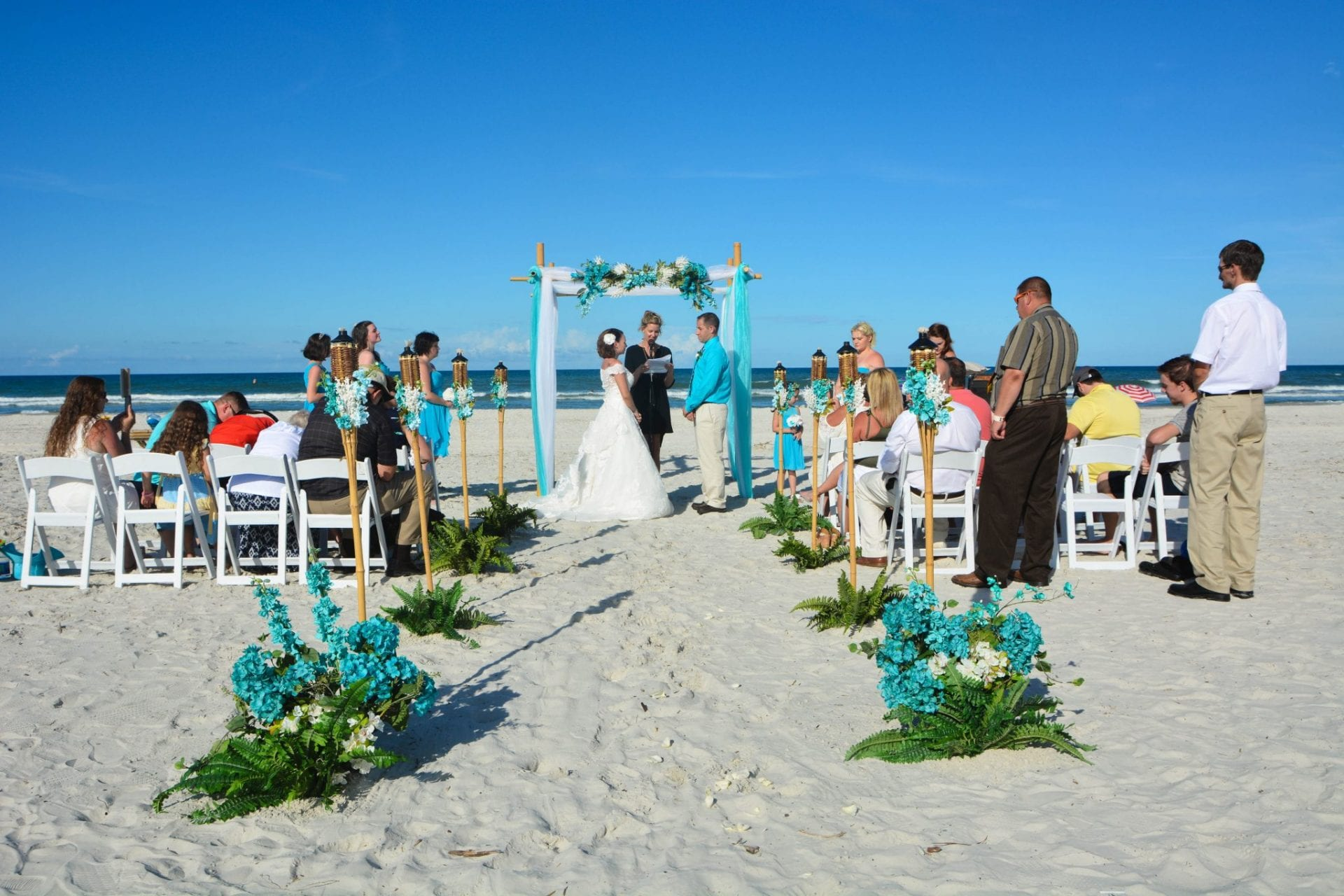 Teal draped bamboo wedding arch on Florida beach with couple saying vows