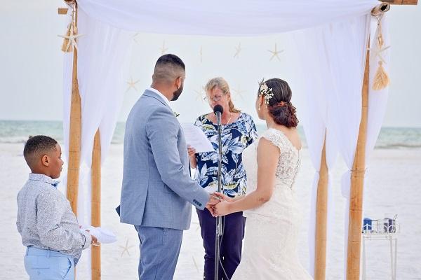 Wedding couple under starfish canopy on Siesta Key Beach saying vows