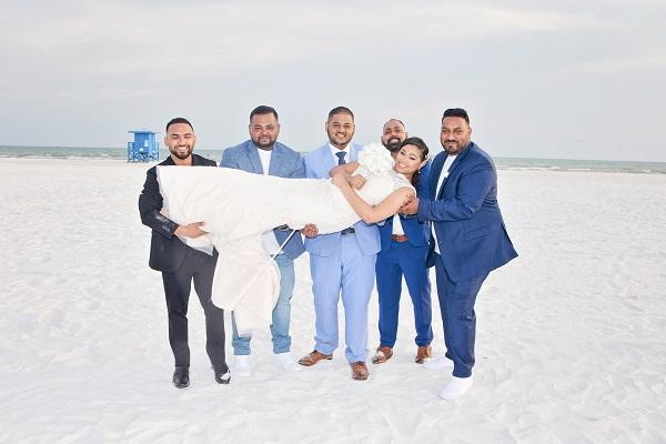 Bride is carried by groomsmen on Siesta Key Beach