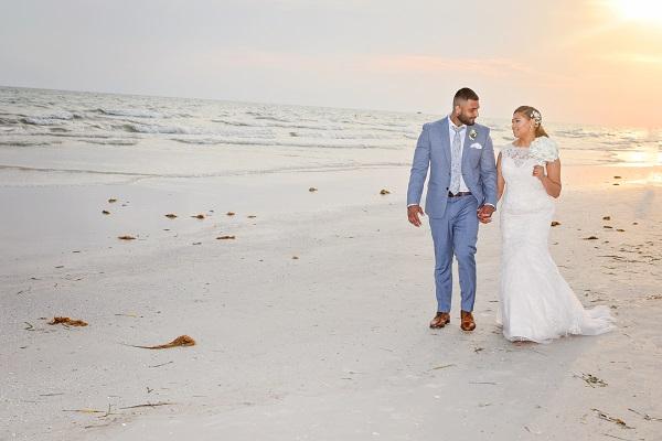 Couple walks on Siesta Key beach at sunset after wedding