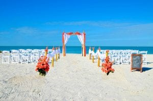 Florida Beach Wedding packages with coral and white material, chairs, officiant and photographer.