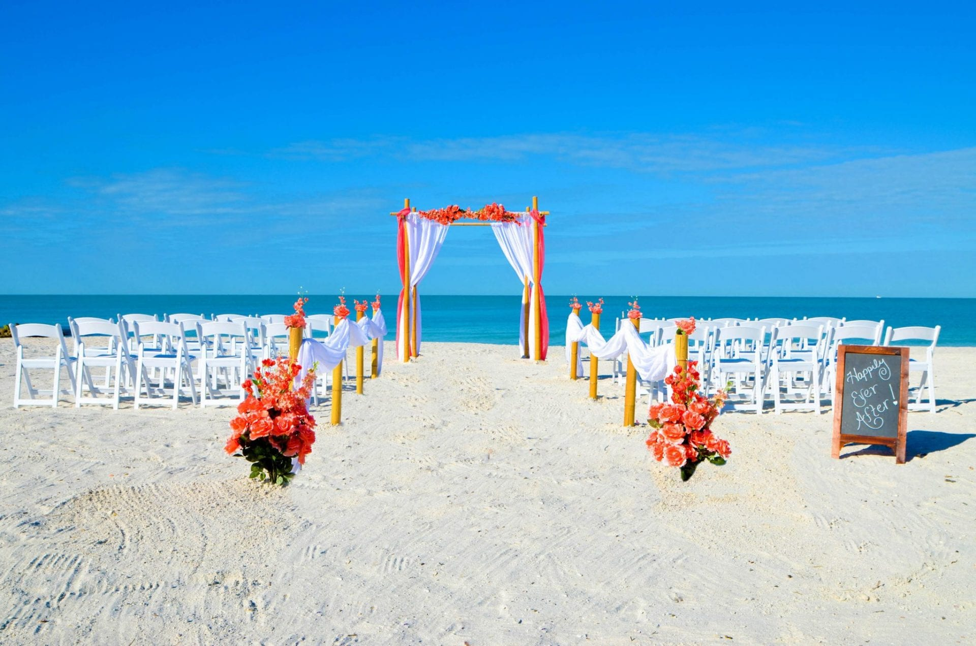 Coral color wedding arch on the beach with chairs