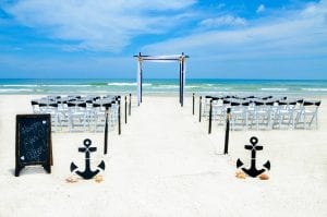 A classic black and white look with banded deluxe resin chairs, chalkboard and anchors with shells start this isleway at a Florida Beach Wedding Ceremony. St. Augustine Elopement