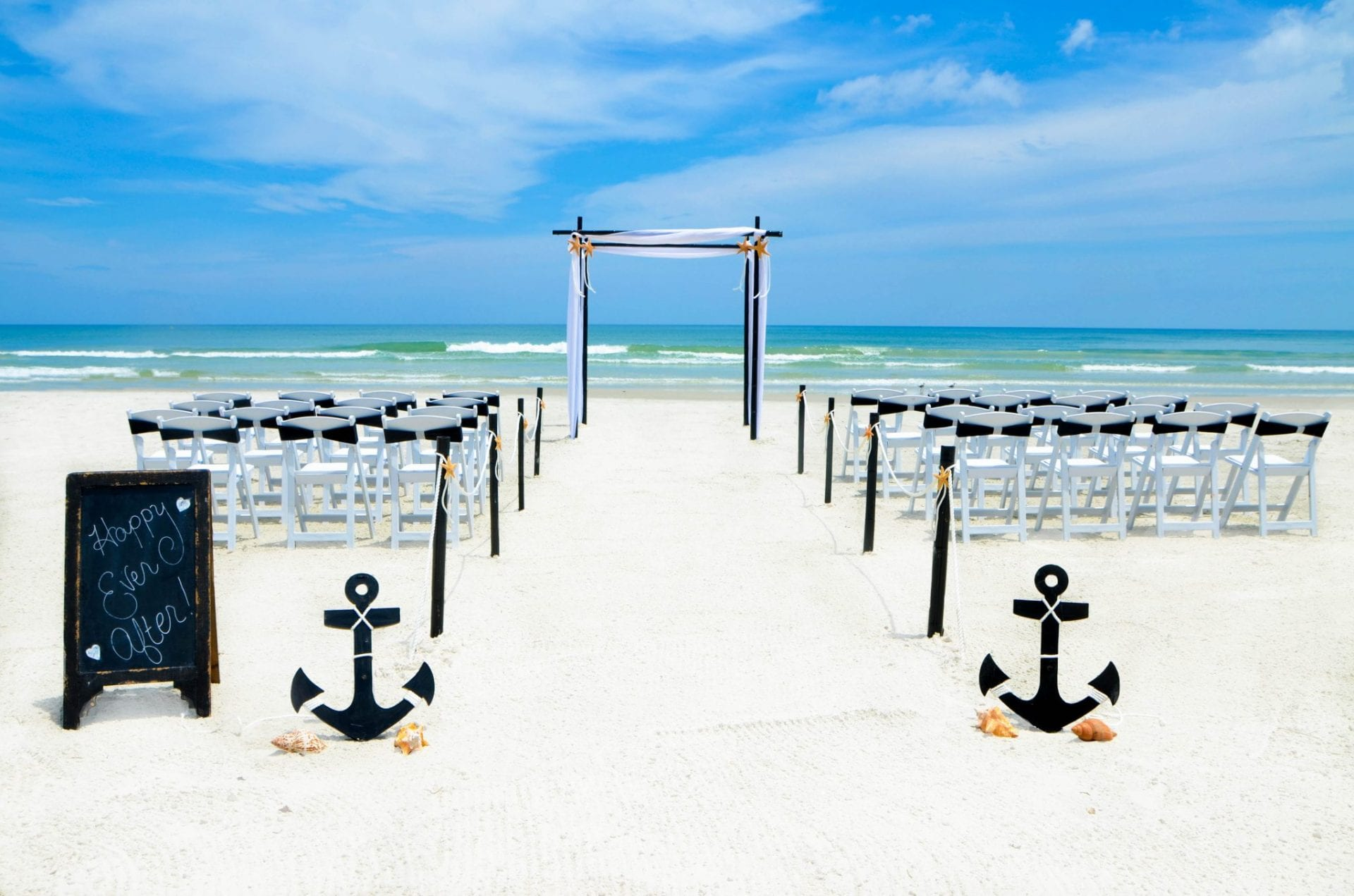 Black draped bamboo wedding arch on the Florida beach with chairs