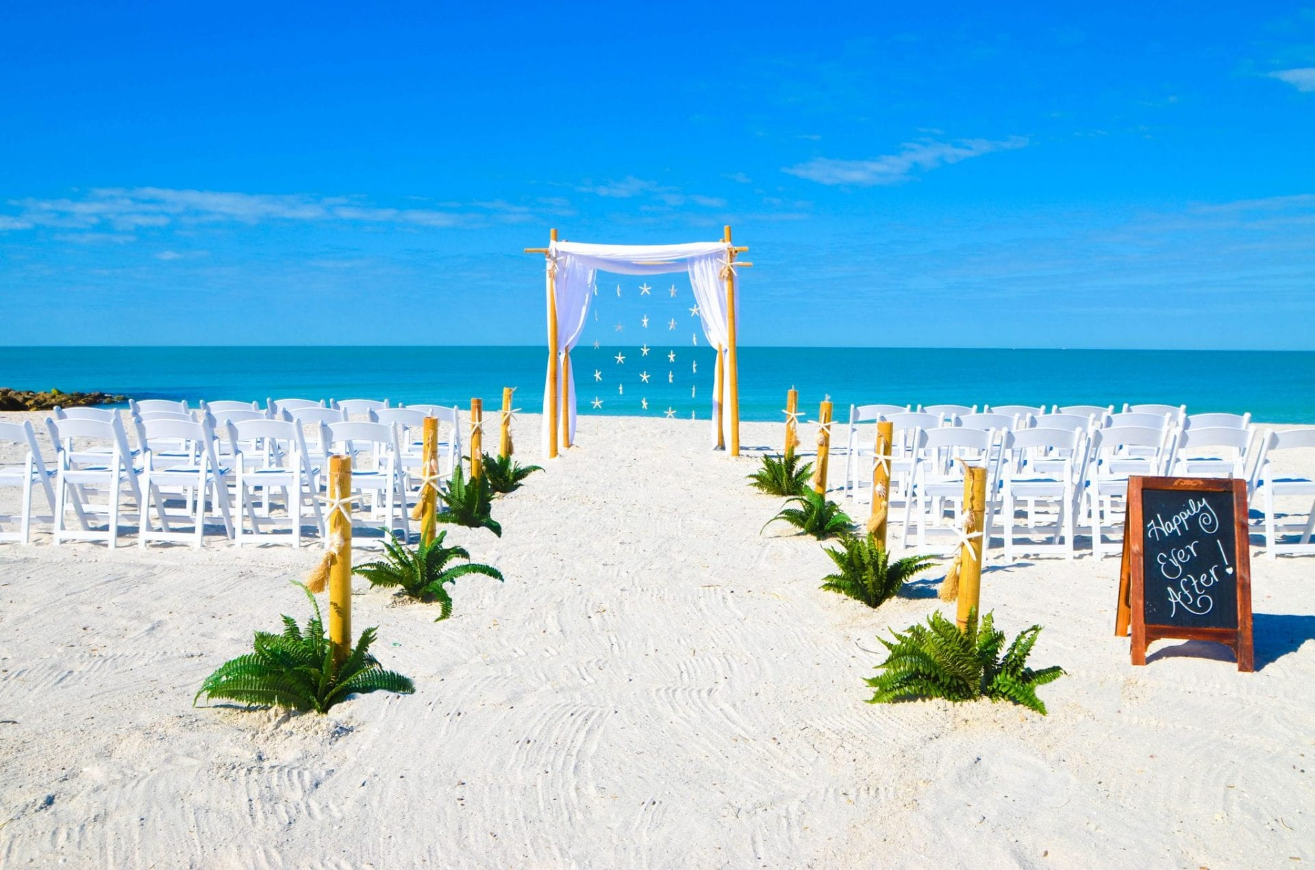 Draped wedding arch with starfish and chairs on Clearwater beach