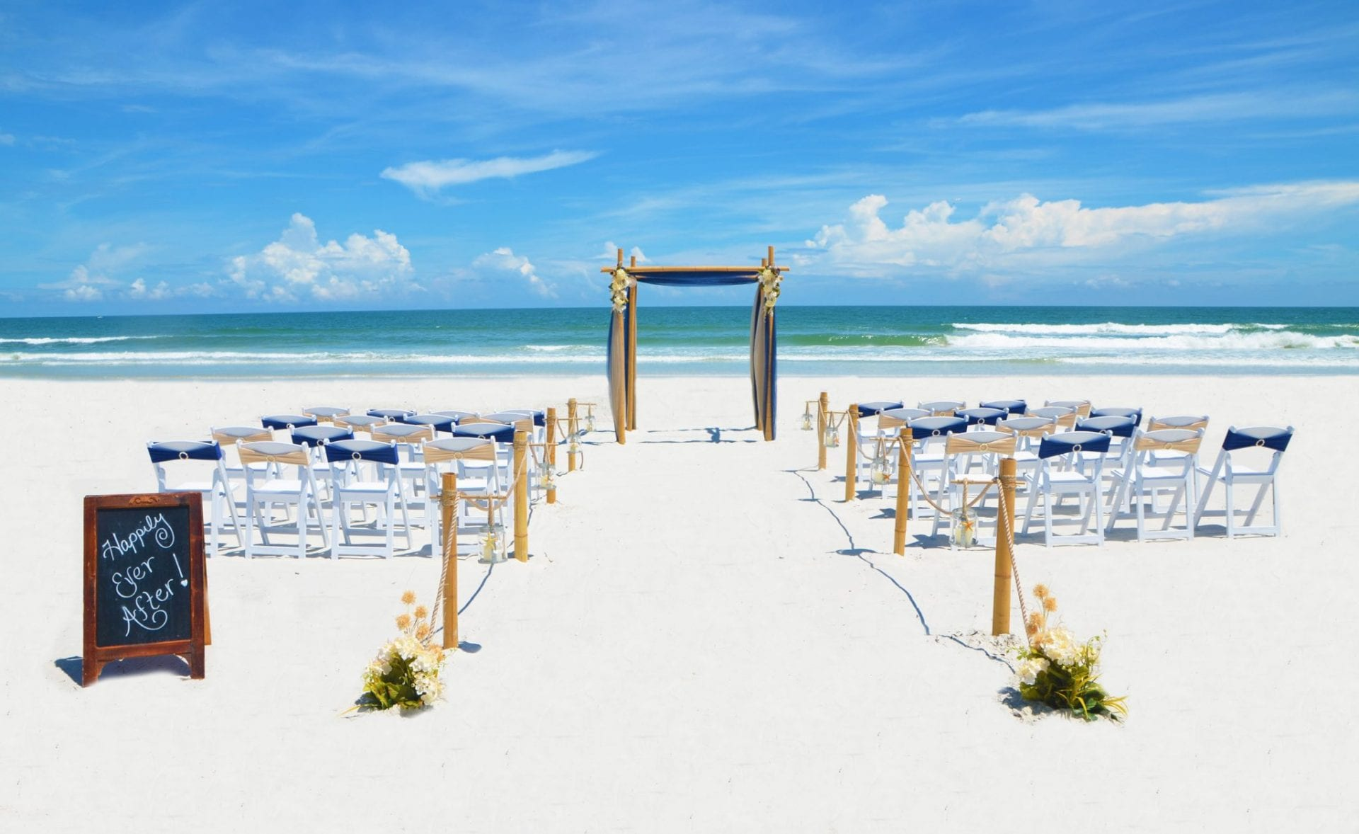 Blue and gold draped wedding arch on Florida beach with chairs