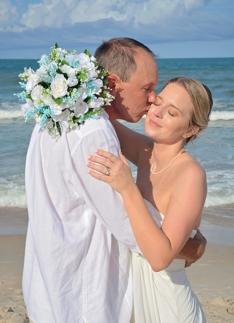 St. Augustine bride and groom kiss on the beach after their wedding with flowers