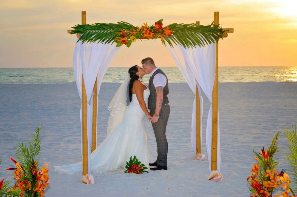 Small Beach Wedding with couple kissing under arch in Florida