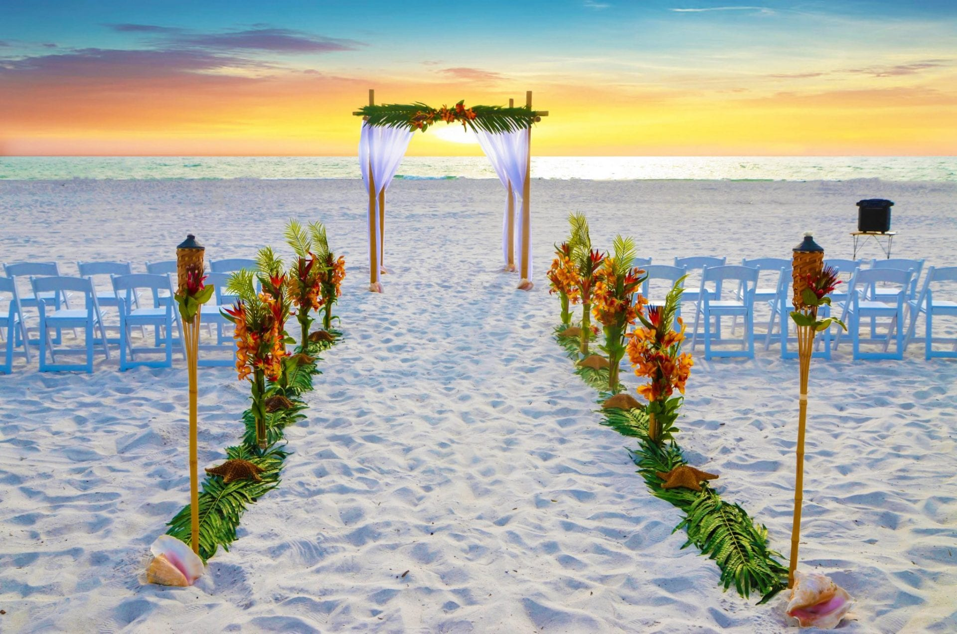 Tropical wedding arch on Siesta Key beach with chairs