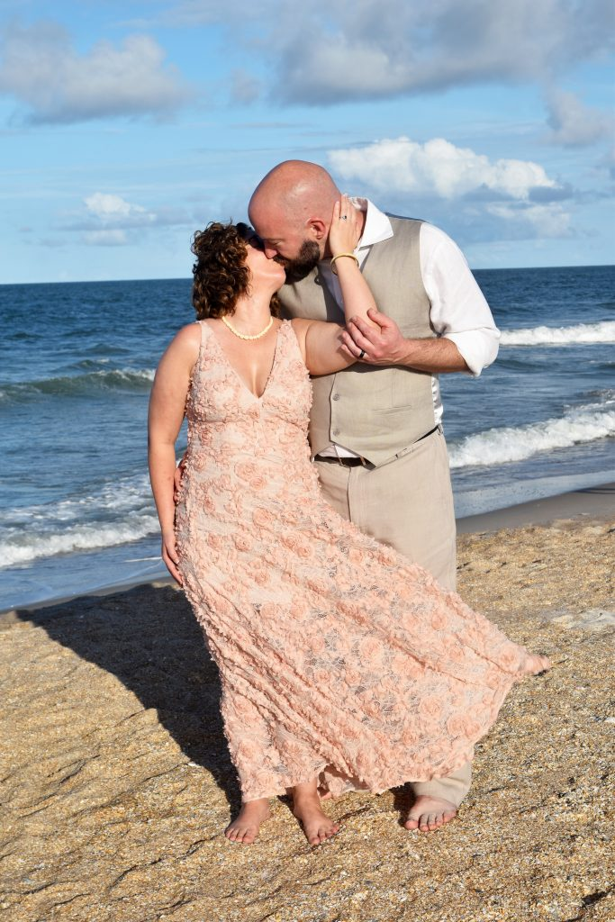 Bride in peach wedding dress married on the beach