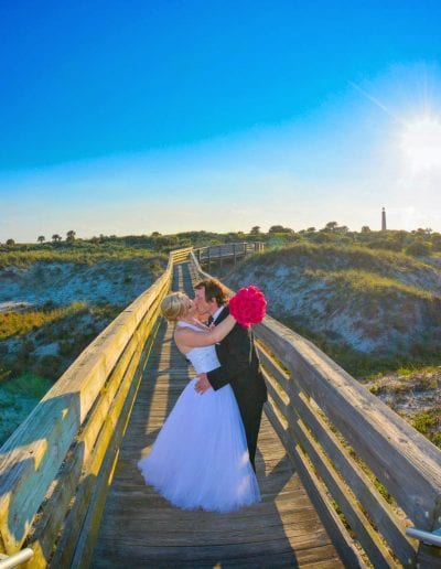 Daytona Beach Wedding couple at Ponce Inlet embraces on walkway as sun goes down