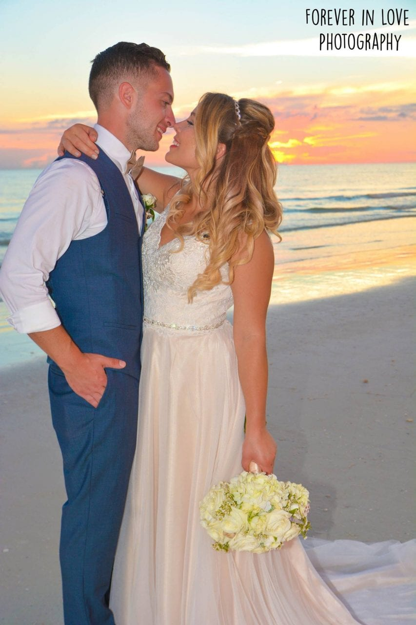 Couple just married at sunset beach wedding ceremony