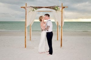 A bride and groom share their first kiss during one of our Siesta Key beach Weddings.