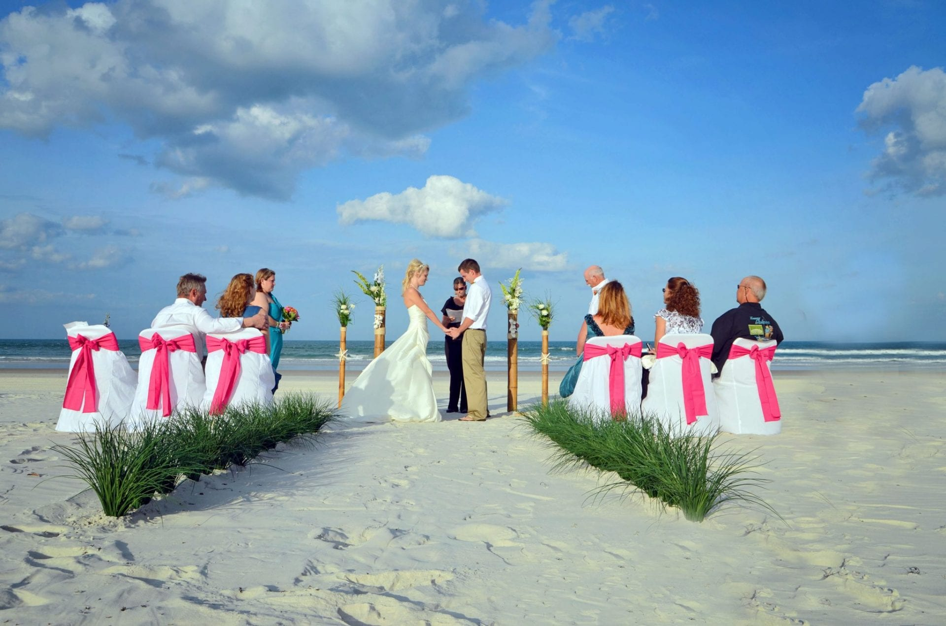 couple holding hands at Florida beach wedding with guests