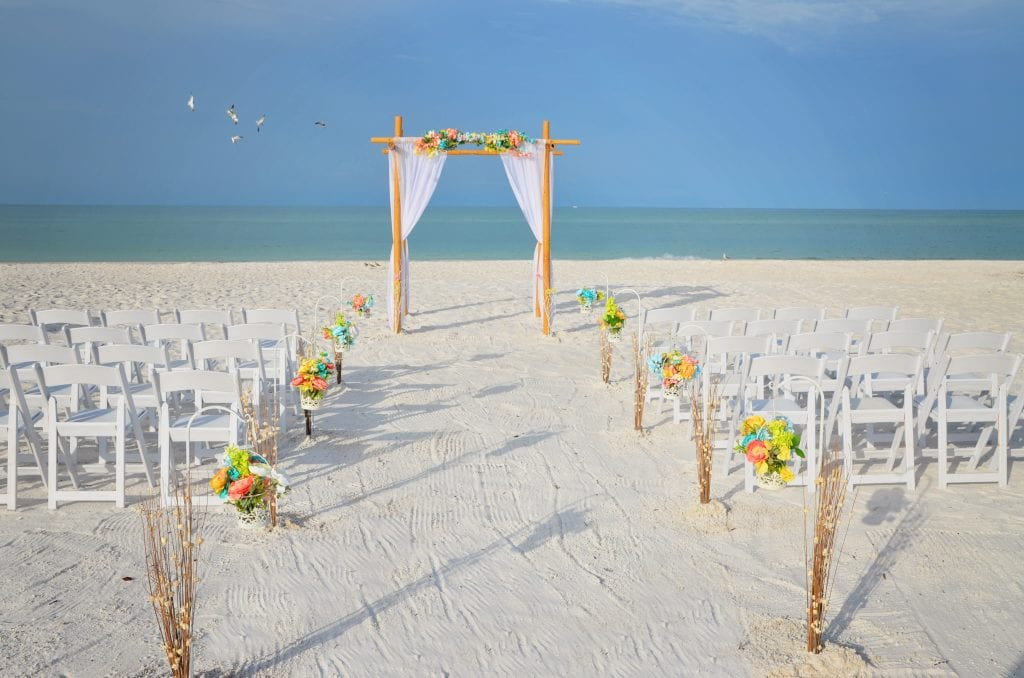 Pastel bamboo wedding arbor on the Gulf beach with chairs