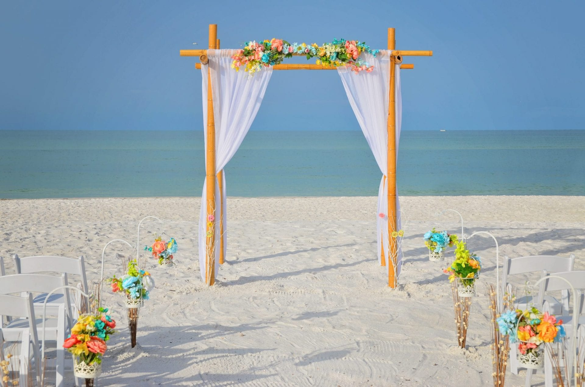 Floral bamboo draped wedding arch setup on Florida oceanfront
