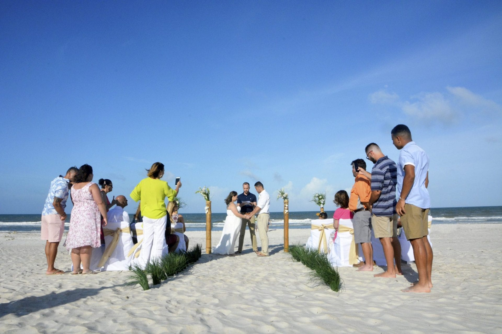 Couple holding hands on the beach saying vows with officiant